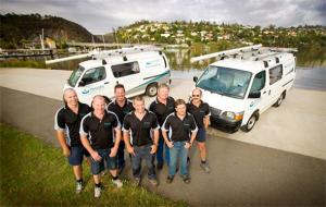 plumbers in Bellevue, WA pose with work vans